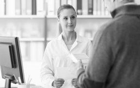 farmaceutka rozmawia z klientem, w rękach trzyma dokument, w tle półki z lekami