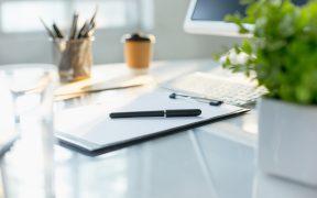 leżące na biurku notatnik z długopisem, klawiatura i monitor, szklanka wody
