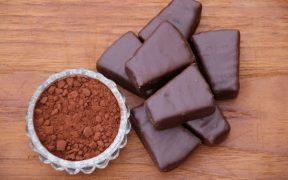 kakao w proszku w filiżance i czekoladki leżące na blacie