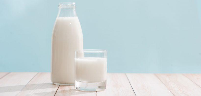szklanka i szklana butelka pełna mleka stojące na stole